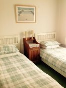 The twin bedroom is carpeted and has large wall cupboards and wardrobes